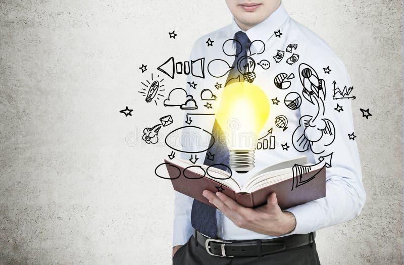 Geschäftsmann hält ein Buch mit Fliegen um Geschäftsikonen und eine Glühlampe als Konzept der neuen Geschäftsideen stockbilder