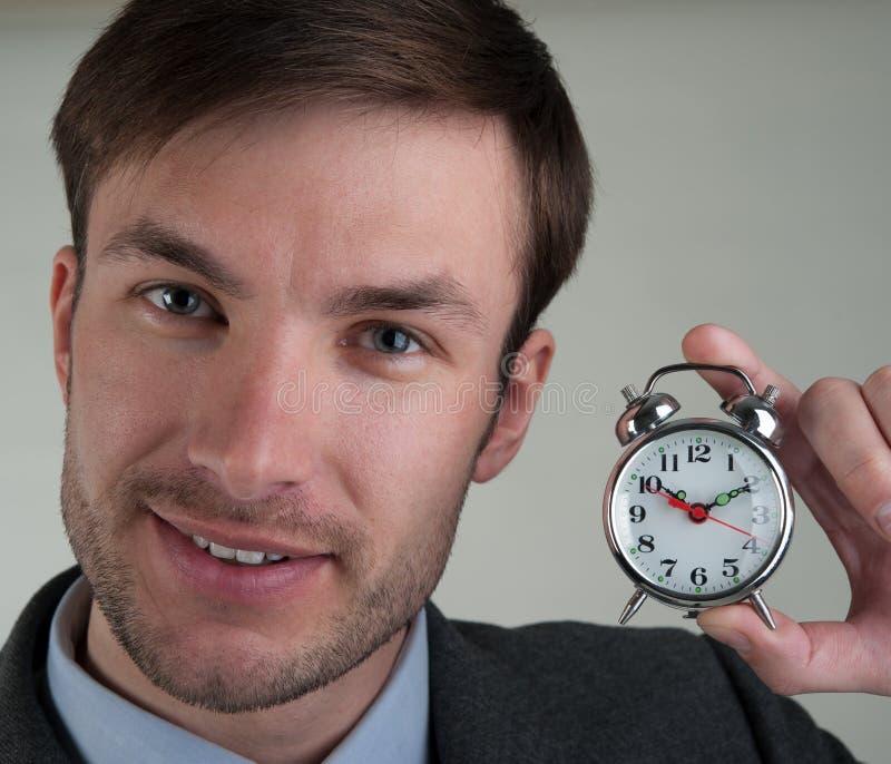 Geschäftsmann hält einen Wecker lizenzfreies stockfoto