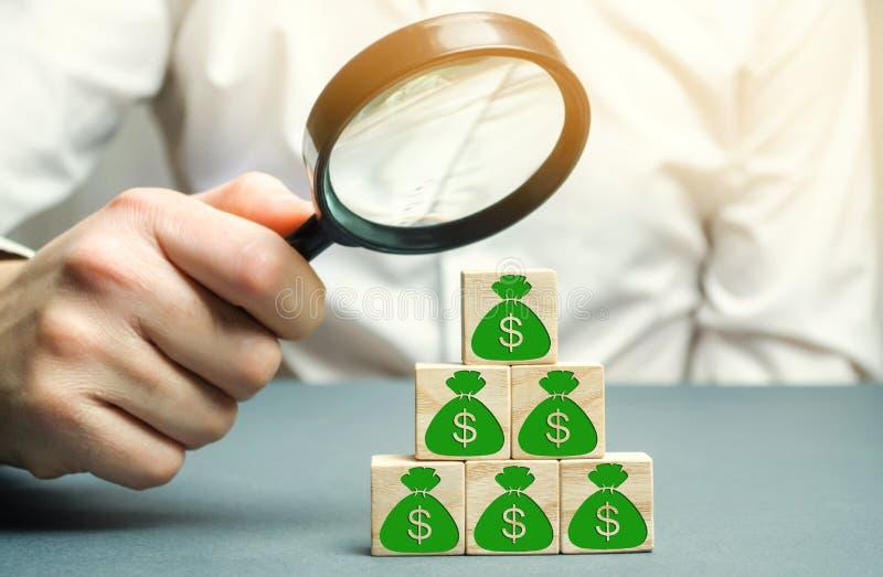 Geschäftsmann hält Lupe über Würfeln mit Dollar Analyse von Gewinnen und von Einkommen in der Firma Verteilung des Geldes lizenzfreies stockfoto