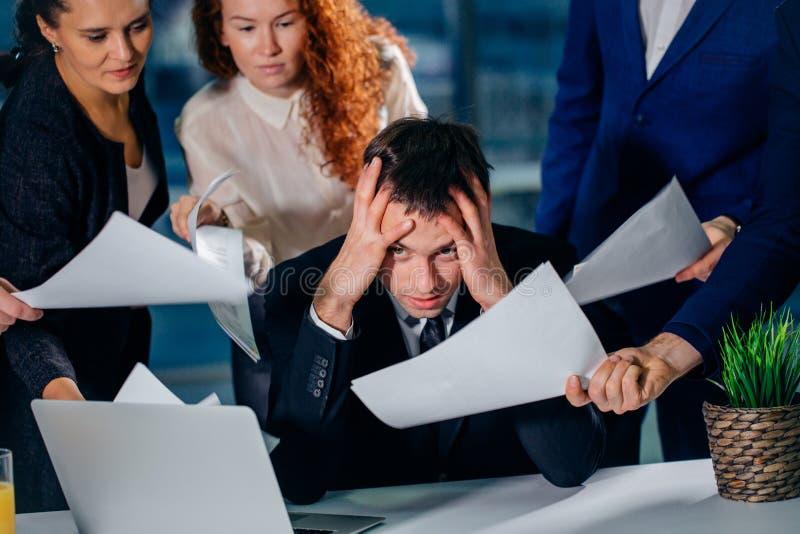 Geschäftsmann halten Haupt mit den Händen umgeben von den Kollegen mit Dokumenten lizenzfreies stockbild