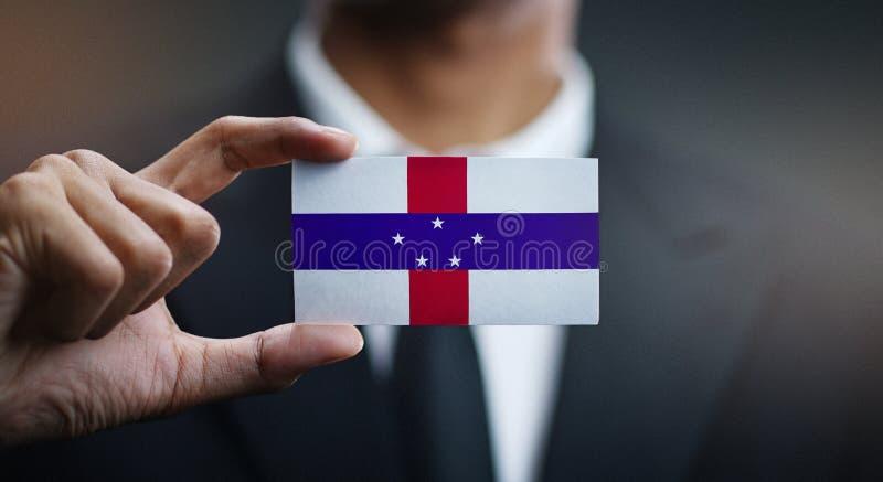 Geschäftsmann Holding Card von Niederländische Antillen-Flagge lizenzfreie stockbilder