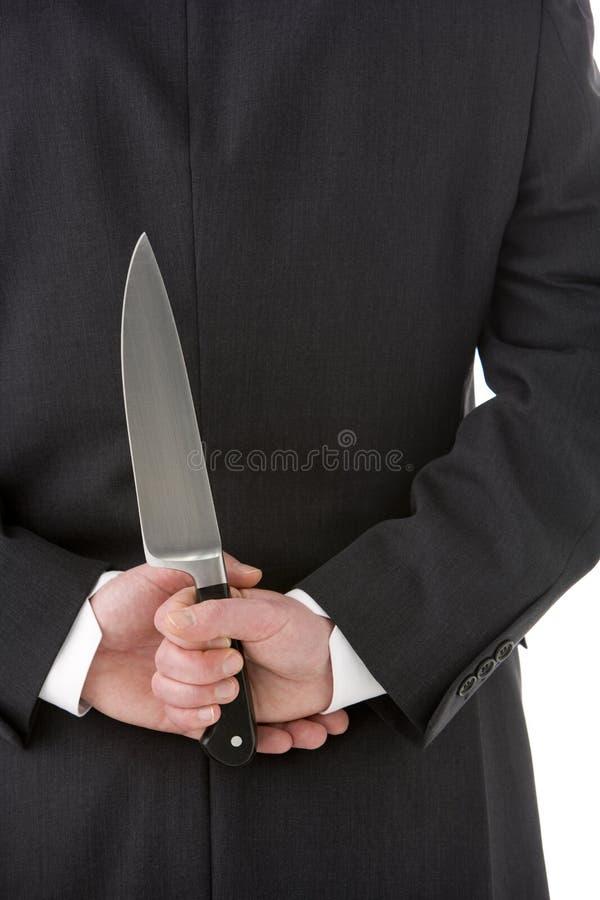 Geschäftsmann-Holding-Messer hinter seinem zurück stockbild