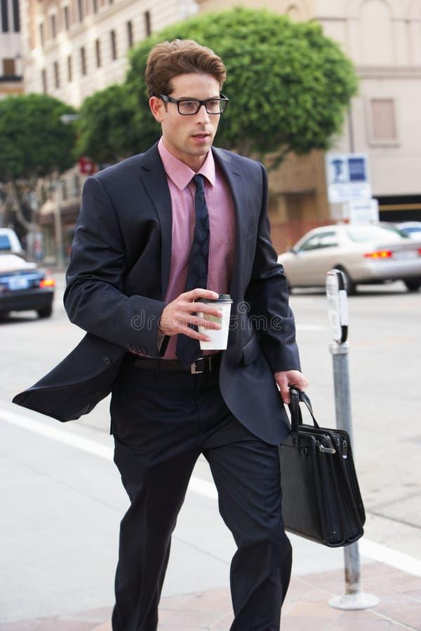 Geschäftsmann Hurrying Along Street, das Mitnehmerkaffee hält stockbild