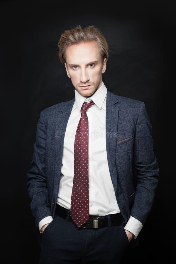 Geschäftsmann im Anzug auf schwarzem Hintergrund Junger Mann lizenzfreies stockfoto
