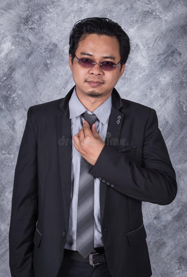 Geschäftsmann im Anzug, der seins Bindung regelt stockbild