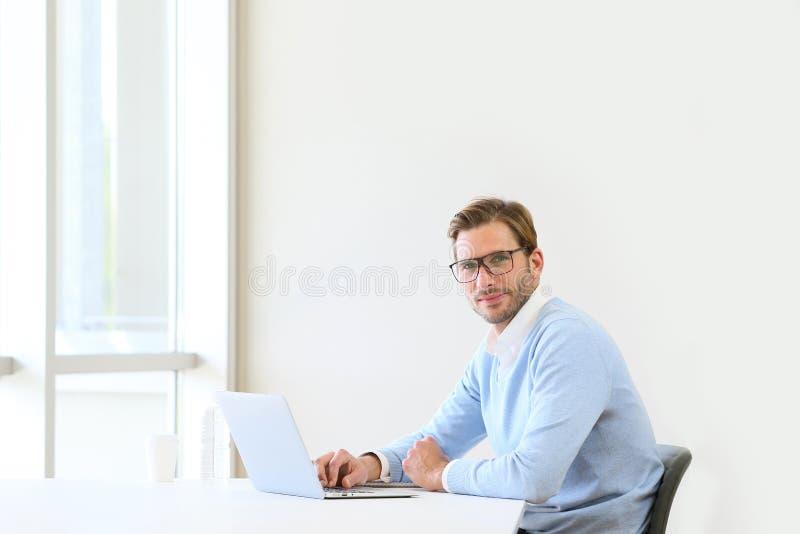 Geschäftsmann im Büro, das an Laptop arbeitet lizenzfreie stockfotografie