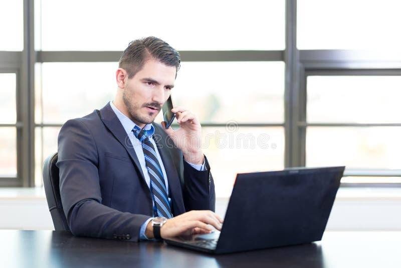 Geschäftsmann im Büro, das an Laptop-Computer arbeitet lizenzfreie stockfotografie