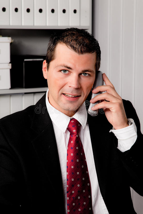 Geschäftsmann im Büro mit Telefon lizenzfreies stockbild