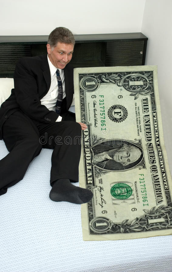 Geschäftsmann im Bett mit dem übermächtigen Dollar lizenzfreies stockbild