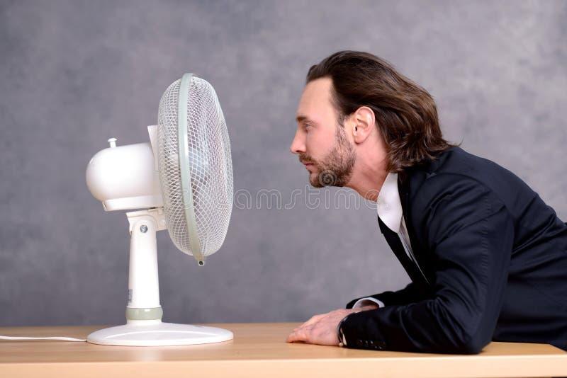 Geschäftsmann im dunklen Anzug, der vor Ventilator sitzt lizenzfreie stockbilder