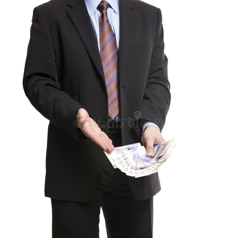 Geschäftsmann im dunklen Anzug zeigt eine Verbreitung von 20 britischen Pfunden Suite lizenzfreies stockfoto