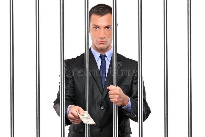 Geschäftsmann im Gefängnis, das Bestechungsgeld gibt stockfotografie
