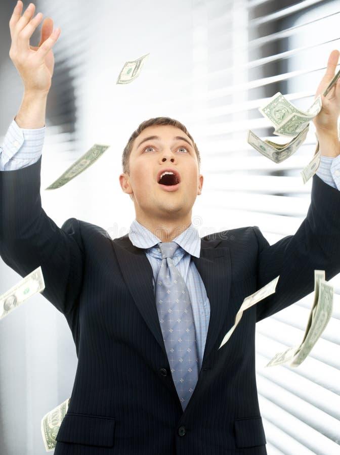 Geschäftsmann im Geldregen zuhause lizenzfreie stockbilder