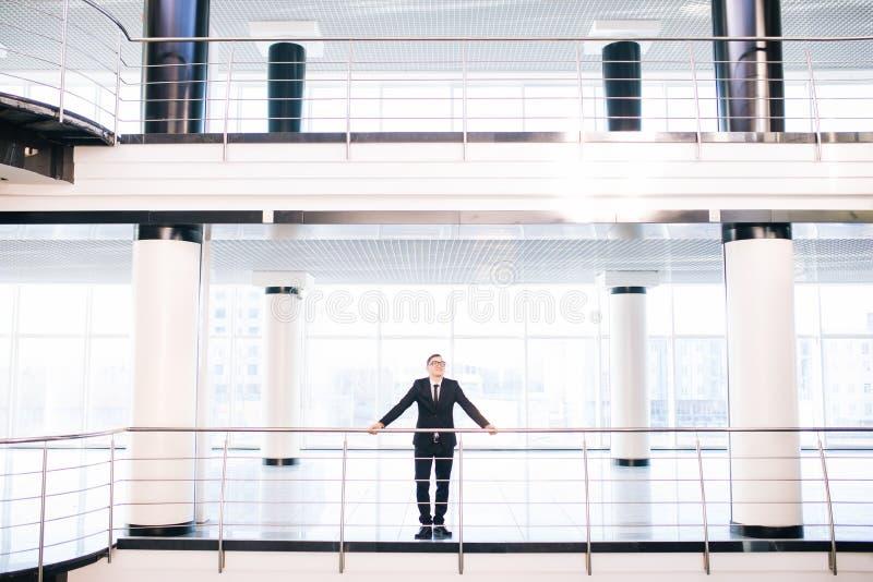 Geschäftsmann im Großen Büroblick um alle Arbeitshalle stockbild