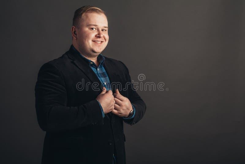Geschäftsmann im schwarzen Anzug auf schwarzem Hintergrund stockfotografie