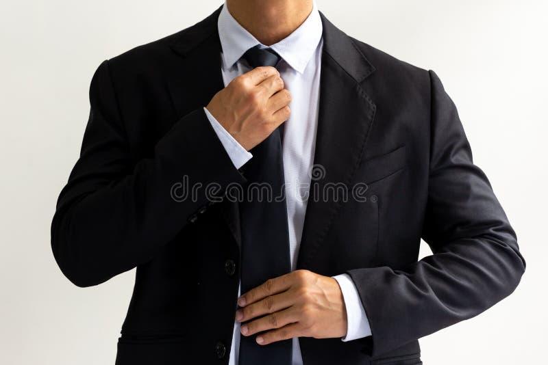 Geschäftsmann im schwarzen Anzug, der die Krawatte bindet stockfotografie