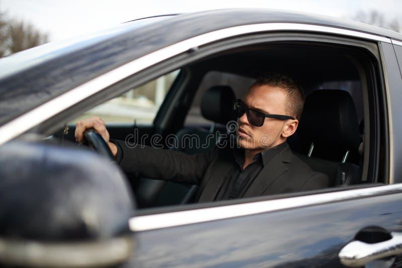 Geschäftsmann im schwarzen Anzug, der hinter Rad sitzt stockfotos