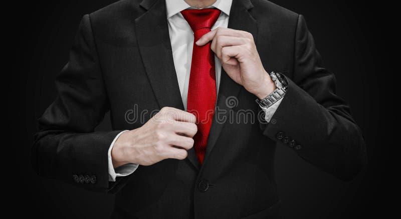 Geschäftsmann im schwarzen Anzug, der rote Krawatte auf schwarzem Hintergrund bindet lizenzfreies stockbild