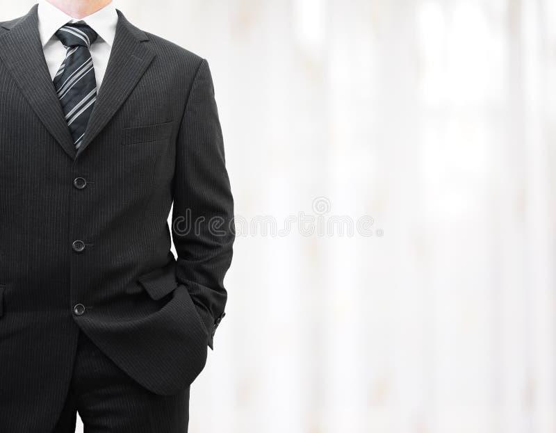 Geschäftsmann im schwarzen Anzug mit der Hand in der Tasche mit unscharfem backg lizenzfreie stockfotografie