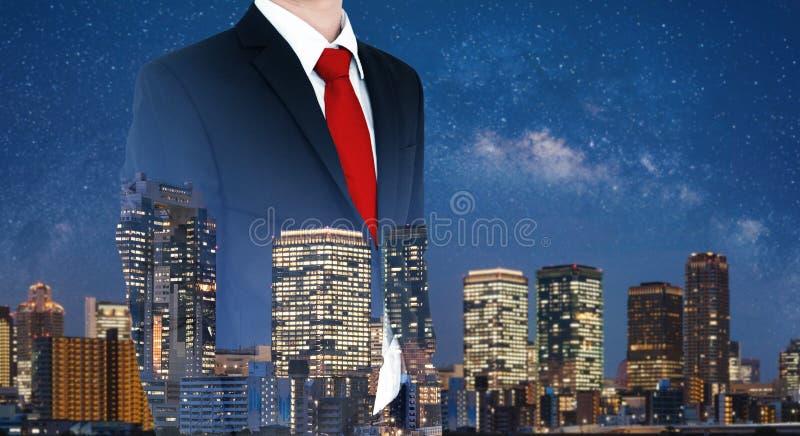 Geschäftsmann im schwarzen Anzug und in der roten Krawatte, mit Doppelbelichtung der Stadt nachts lizenzfreie stockfotografie