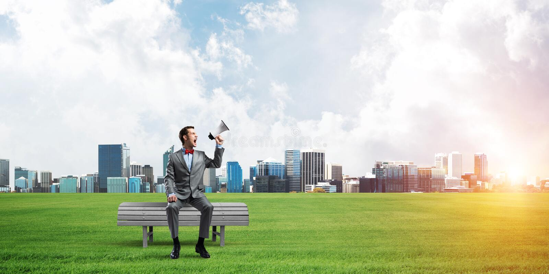 Geschäftsmann im Sommerpark etwas im Lautsprecher und im Stadtbild am Hintergrund ankündigend stockfotografie