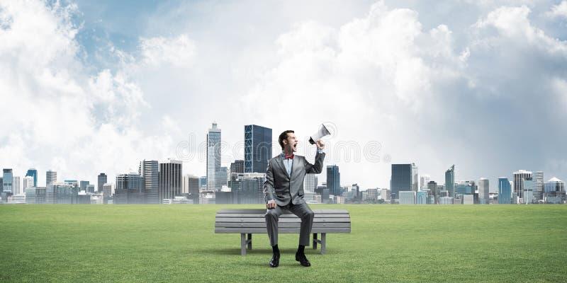Geschäftsmann im Sommerpark etwas im Lautsprecher und im Stadtbild am Hintergrund ankündigend stockfoto