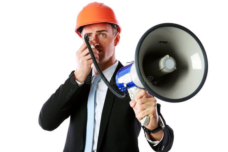 Geschäftsmann im Sturzhelm schreiend mit Megaphon lizenzfreies stockfoto