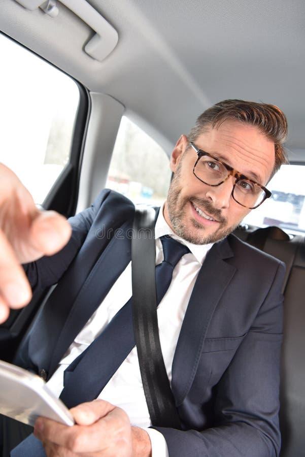 Geschäftsmann im Taxi sprechend mit Fahrer lizenzfreie stockfotografie