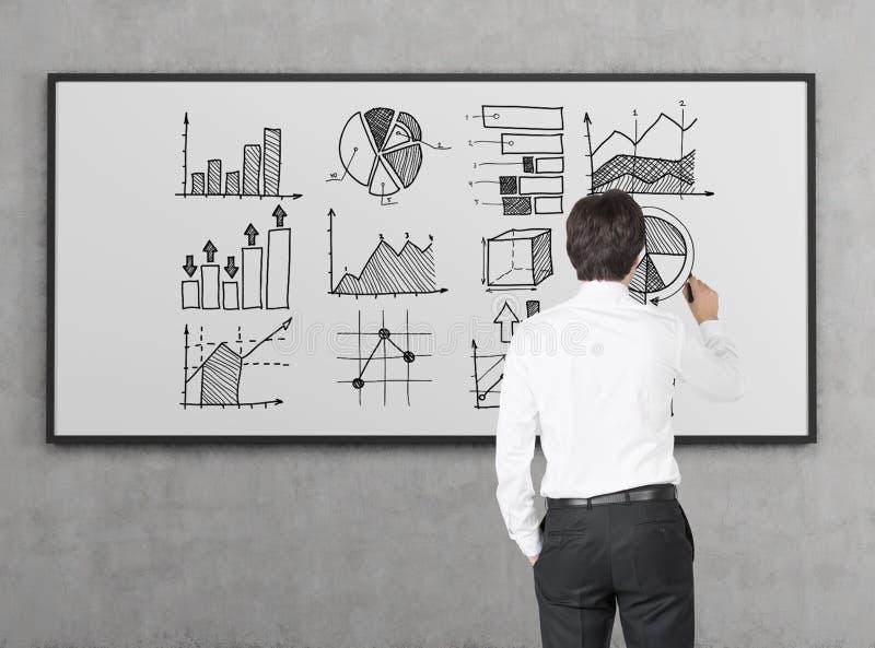 Geschäftsmann im weißen Hemd zeichnet Diagramme auf whiteboard stockfotografie