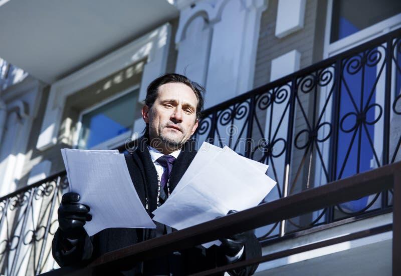 Geschäftsmann im Zweifel, Betrachtendokumente, Tag, im Freien stockbild