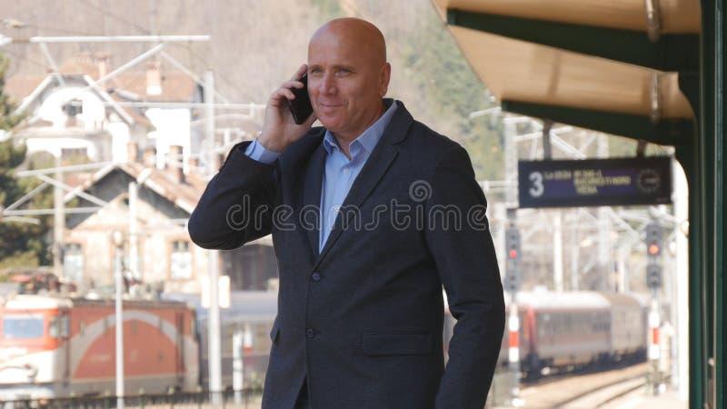 Geschäftsmann Image Smiling und Unterhaltung mit Handy in einem Bahnhof lizenzfreie stockbilder