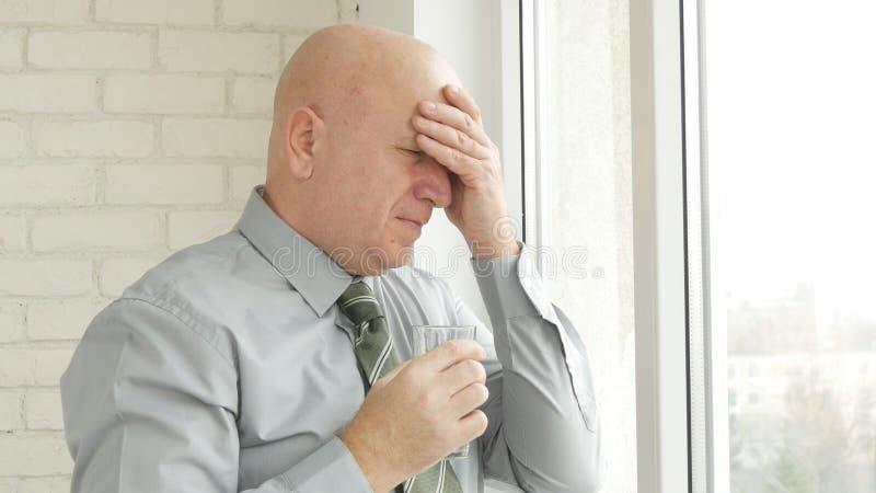 Geschäftsmann Image Suffering Kopfschmerzen mit einem Glas mit Wasser in der Hand stockfotografie