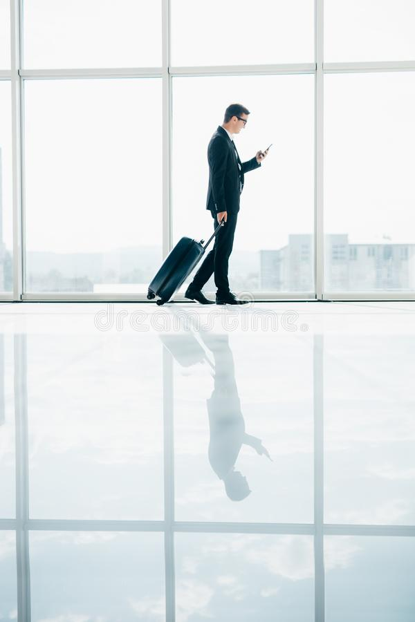 Geschäftsmann am internationalen Flughafen, der auf Terminaltor für die Flugzeugreisereise in der Hand schaut im Telefon sich bew stockfotografie