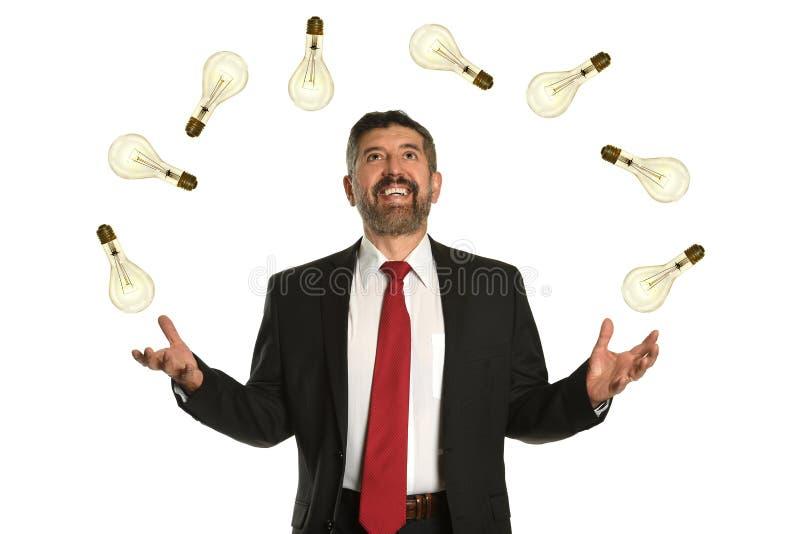 Geschäftsmann Juggling Multiple Lightbilbs stockfoto