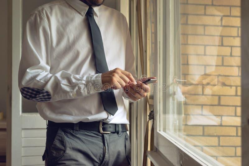 Geschäftsmann klopft intelligentes Mobiltelefon lizenzfreie stockbilder