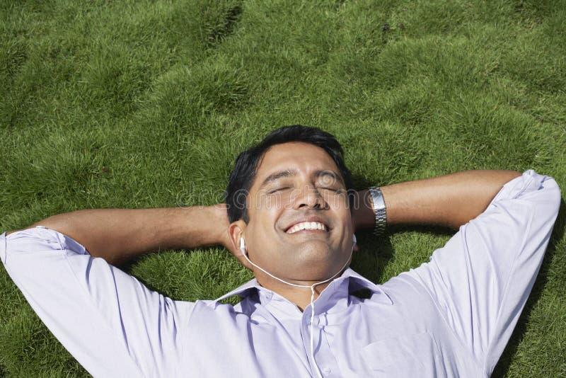 Geschäftsmann Listening Music While, das auf Gras liegt stockfotos