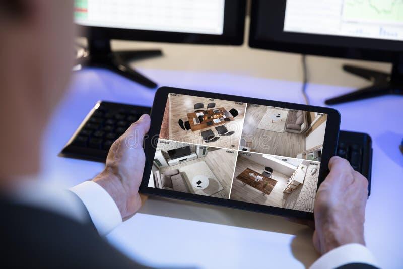 Geschäftsmann-Looking At-Überwachungskamera-Gesamtlänge auf Digital-Tablet lizenzfreie stockfotos