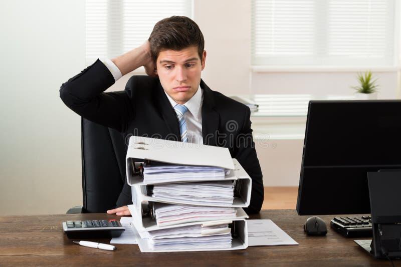 Geschäftsmann Looking At Stack von Ordnern lizenzfreies stockfoto