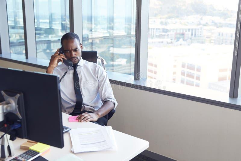 Geschäftsmann Making Phone Call, das am Schreibtisch im Büro sitzt lizenzfreie stockfotografie