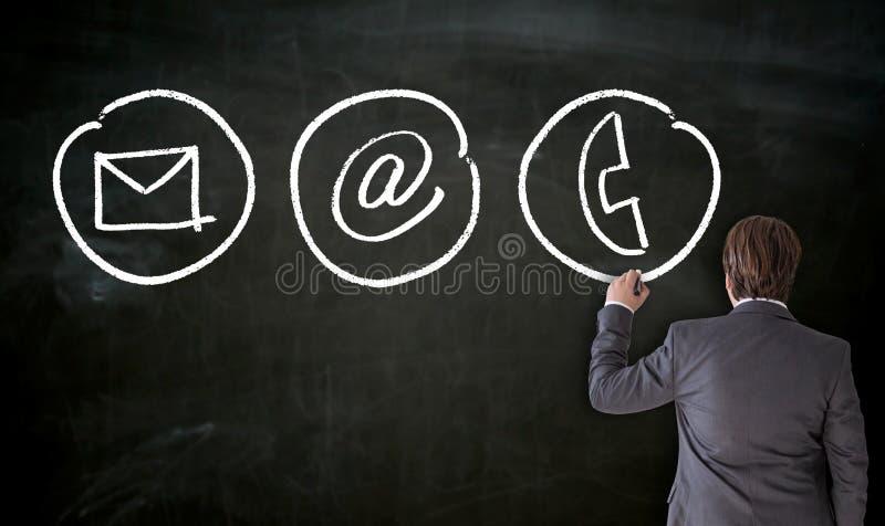 Geschäftsmann malt mit Kreidekontaktwahlen auf Tafel lizenzfreies stockbild