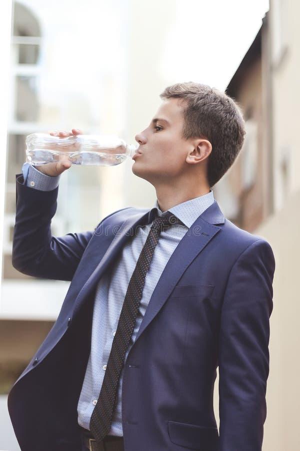 Geschäftsmann mit Anzug mit Wasserflasche und Trinkwasser im Freien Der junge Geschäftsmann trinkt Frischwasser in der Stadt stockbilder