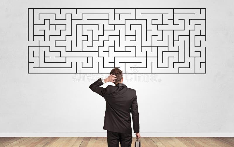 Geschäftsmann mit Blick auf ein Labyrinth an der Wand lizenzfreie stockbilder