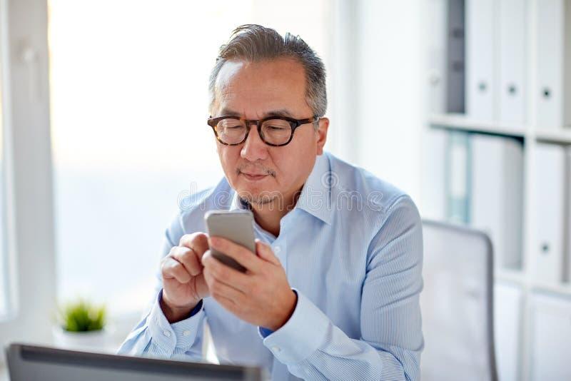 Geschäftsmann mit dem Laptop, der auf Smartphone simst stockfoto