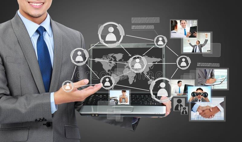Geschäftsmann mit dem Laptop, der das soziale angeschlossen zeigt stockbilder