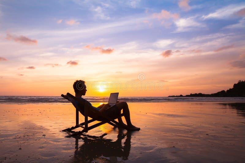 Geschäftsmann mit dem Laptop, der an dem Strand arbeitet lizenzfreie stockbilder