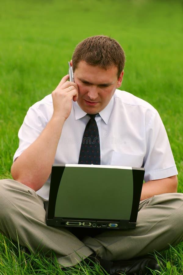Geschäftsmann mit dem Laptop, der im Gras sitzt