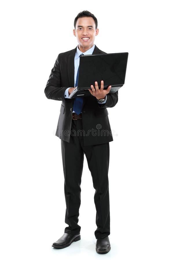 Geschäftsmann mit dem Laptop, der Kamera betrachtet lizenzfreies stockbild