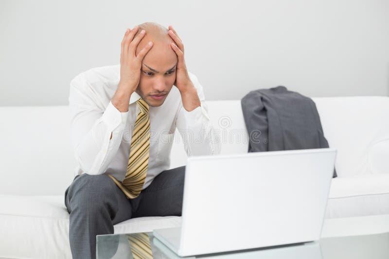 Geschäftsmann mit dem Laptop Haupt zu Hause halten in den Händen stockfotos