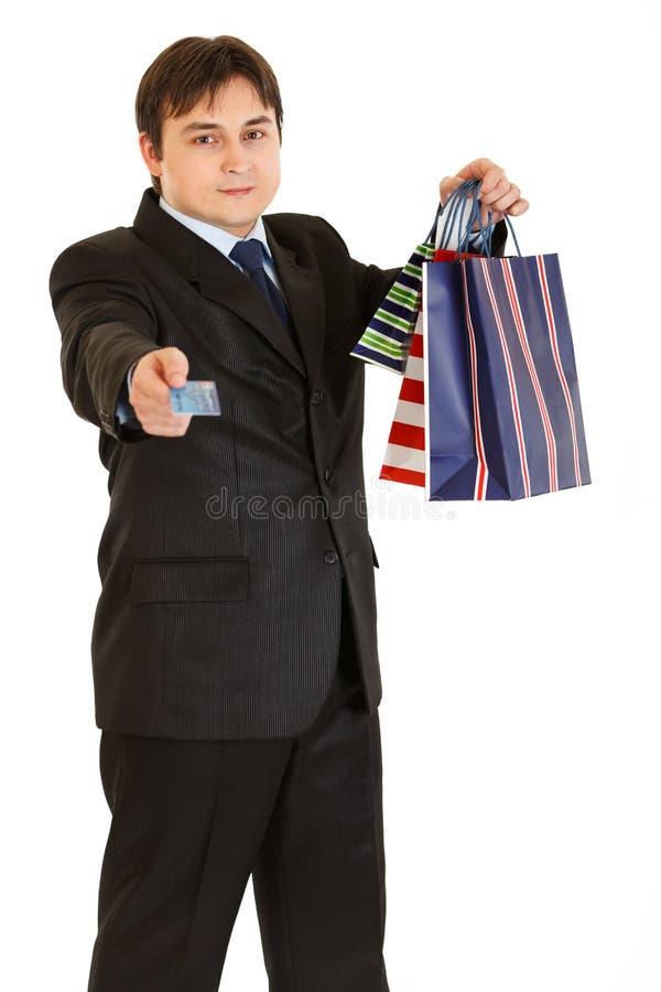 Geschäftsmann mit den Einkaufenbeuteln, die Kreditkarte geben lizenzfreie stockfotografie