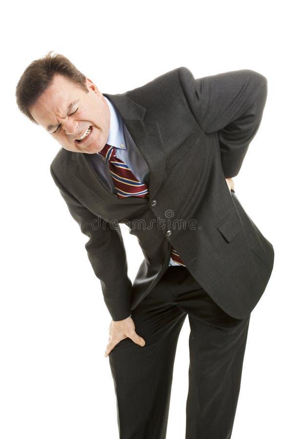 Geschäftsmann mit den rückseitigen Schmerz lizenzfreies stockbild
